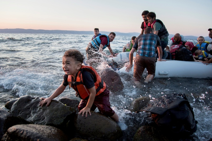 Syrian refugees arriving from Turkey in an inflatable raft. Photo by Andrew McConnell for The New Yorker.